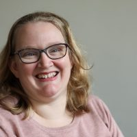 Photograph of Advocate Kim Collinson, a woman with wavy, blonder, shoulder-length hair and blue eyes smiling at the camera. She is wearing thin framed glasses and a pink jumper.