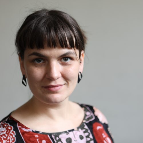 A photo of Communications and Promotions Officer Anja Homburg. A woman with dark brown hair worn up with a straight fringe. She is looking at the camera and smiling with a closed mouth.