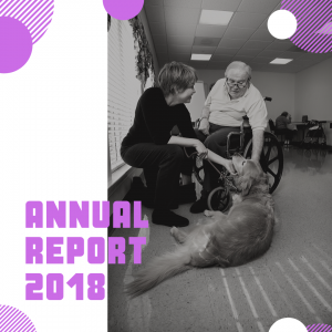 Annual Report 2018 - An older, balding man in a wheelchair and a middle-aged, short-haired woman patting a golden retriever assistance dog.