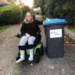 woman in a wheelchair beside a big outdoor bin. The bin has #LifelongLockdown on it