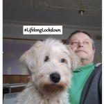 Man with very cute dog on his lap, #lifelonglockdown is written on the screen