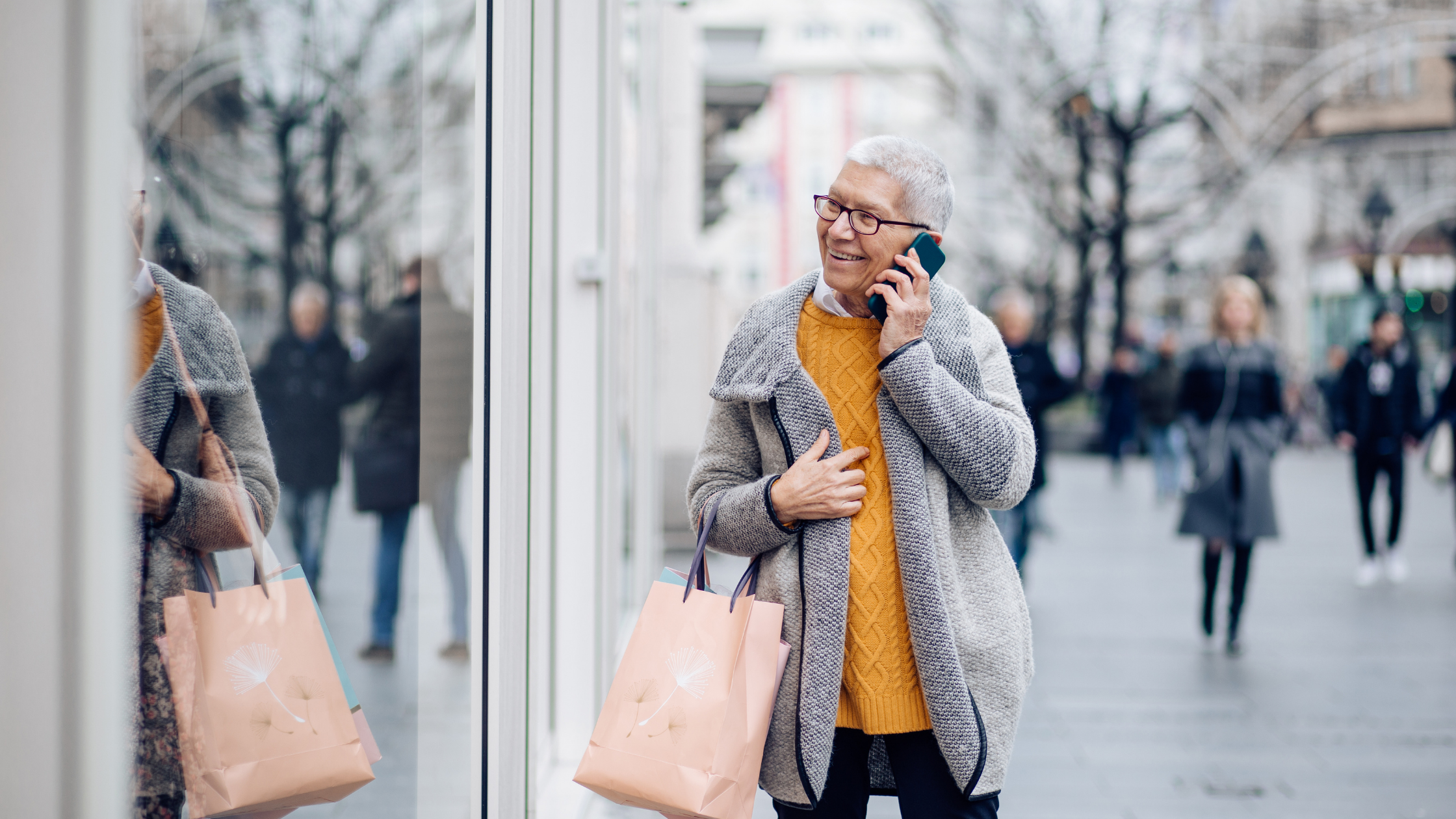 An older woman with short white hair and red rimmed glasses standing on a street with a shopping bag. She is talking on her phone and smiling.