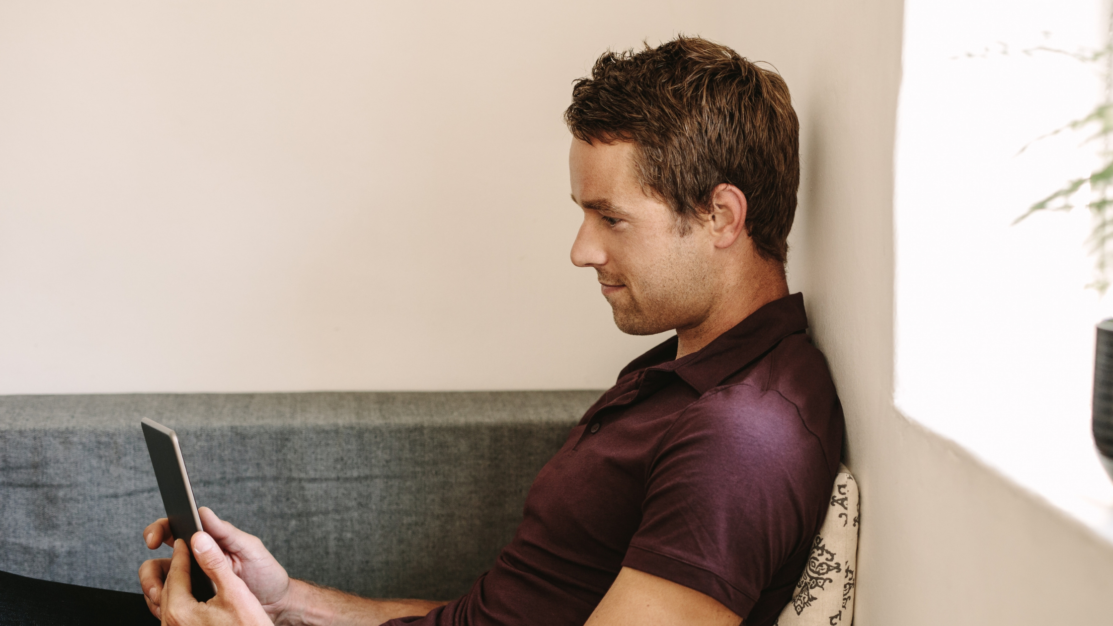 A man in his 30s with short light brown hair and stubble. He is wearing a plum polo shirt sitting on a couch looking at his phone.