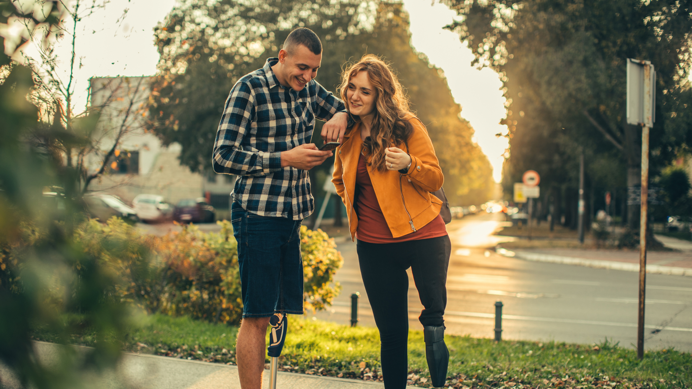 A man and woman standing on a sidewalk. Each has a prosthetic left leg. The man is resting his elbow on the woman's shoulder, looking at his phone. Both are smiling.